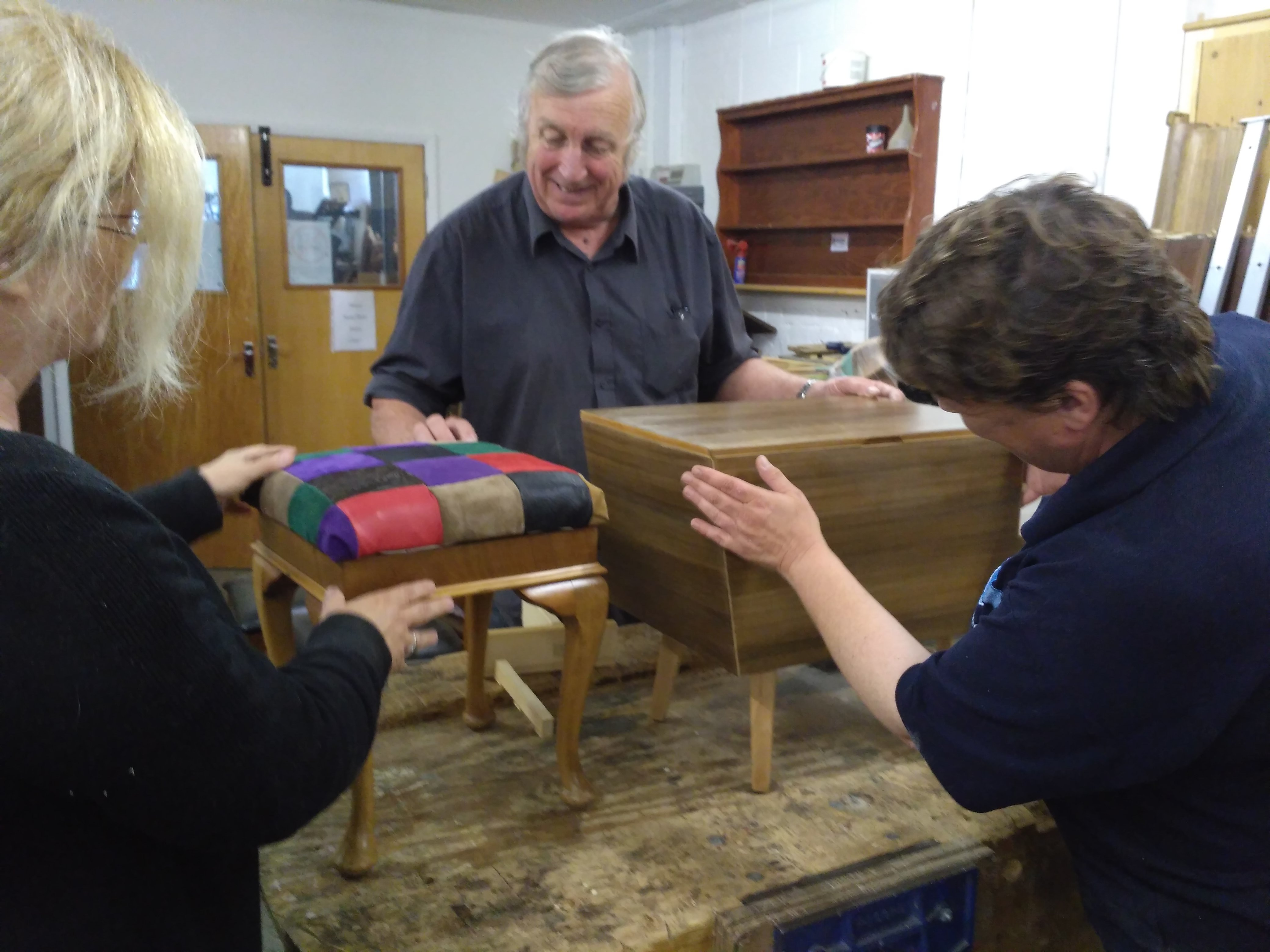 learners admire their finished furniture restoration